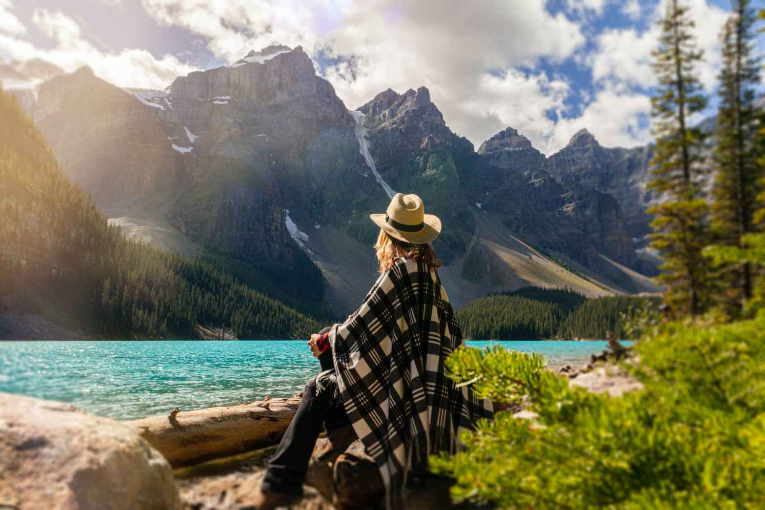 become secure - a woman looks at a scenic view, possibly inspired by the security of the mountains.