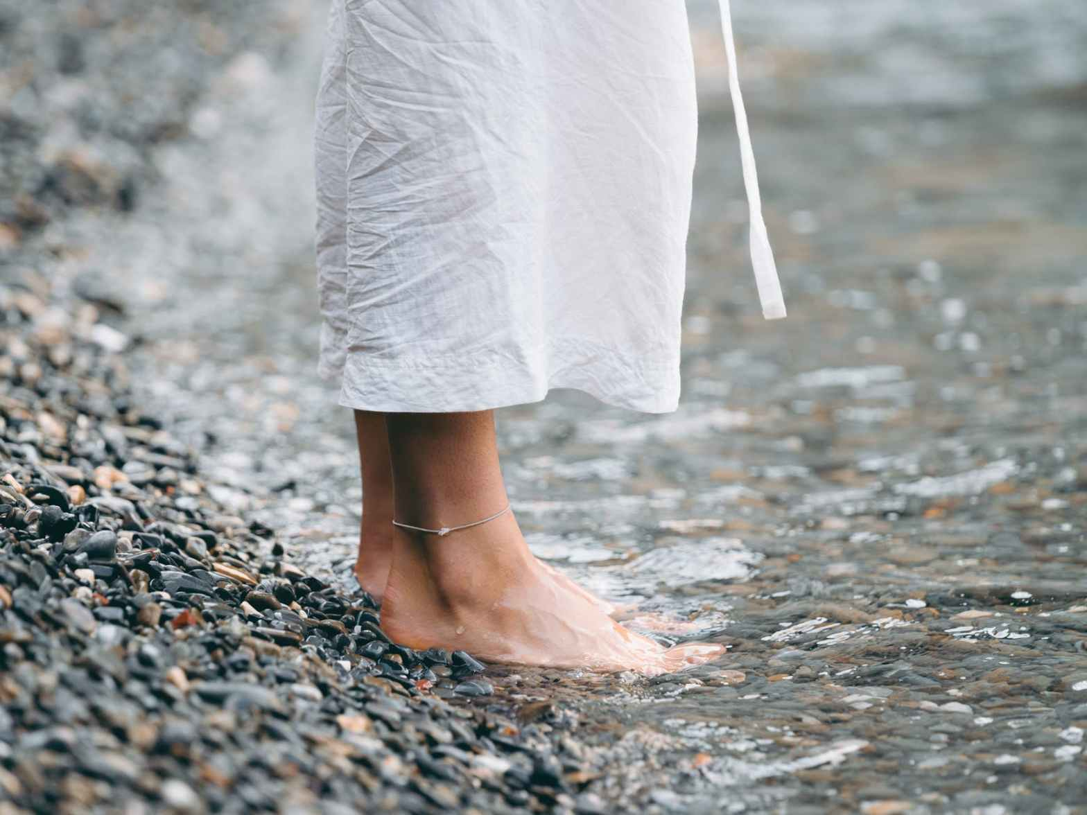 affirmation: I stand firm in my love! A woman's feet standing firmly in the water's edge