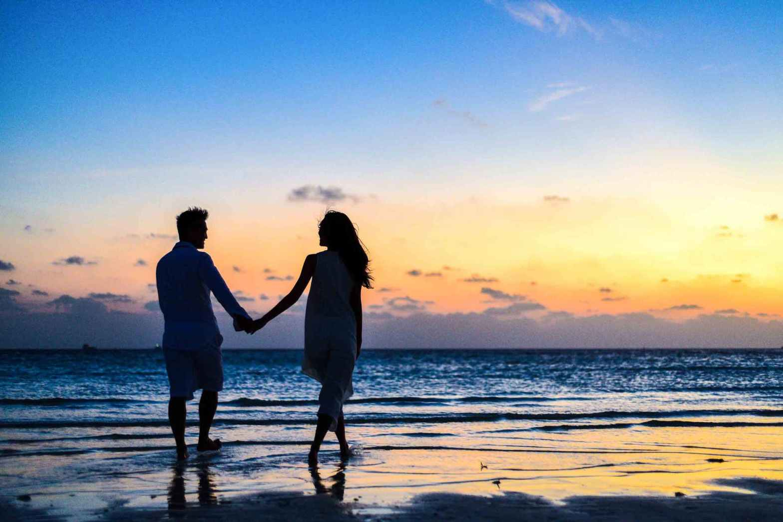 fulfilling relationship - a couple holding hands walking on a beach at sunset